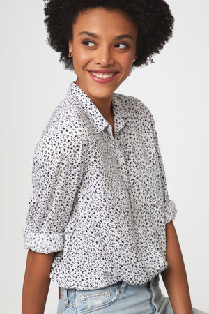 close up of woman wearing a black and white floral, long sleeve, button-down blouse with single chest pocket and drop back hem