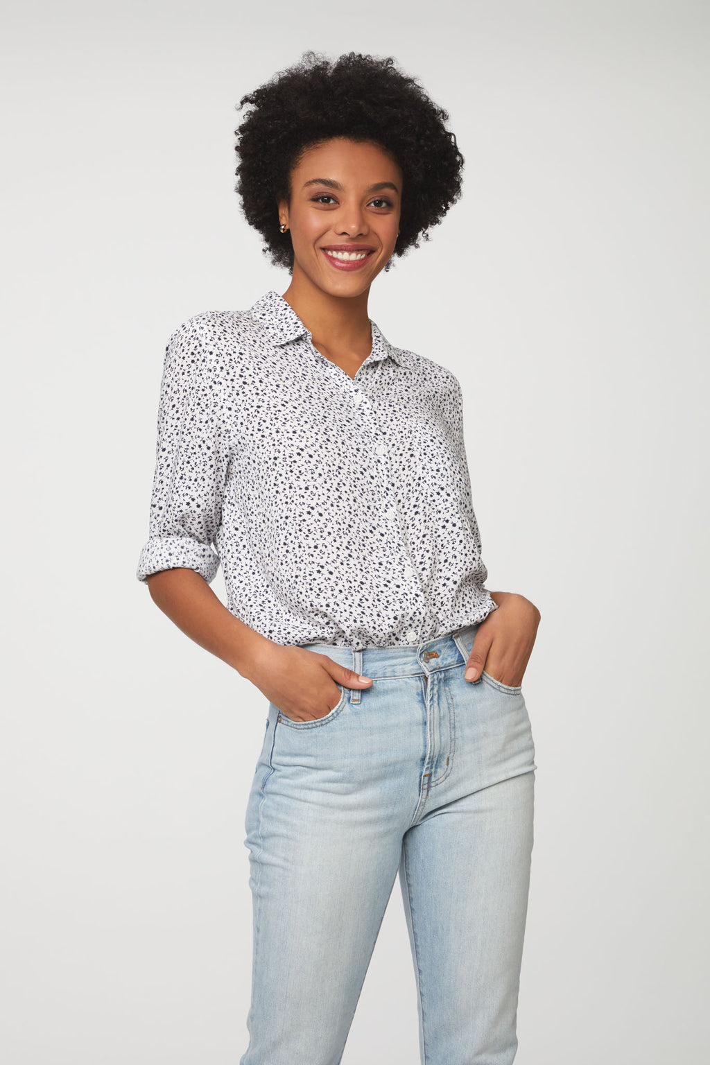 woman wearing a black and white floral, long sleeve, button-down blouse with single chest pocket and drop back hem