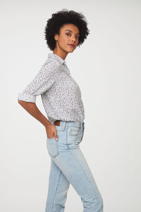 side view of woman wearing a black and white floral, long sleeve, button-down blouse with single chest pocket and drop back hem