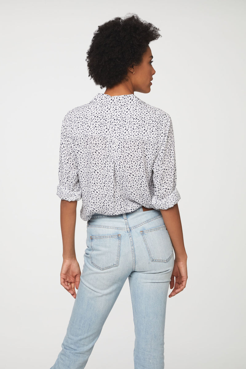 back view of woman wearing a black and white floral, long sleeve, button-down blouse with single chest pocket and drop back hem