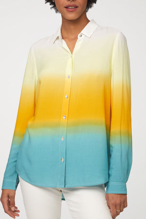 close up view of woman wearing a long sleeve, button-down, yellow, blue and white dip dye shirt