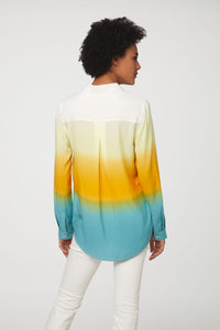 back view of woman wearing a long sleeve, button-down, yellow, blue and white dip dye shirt