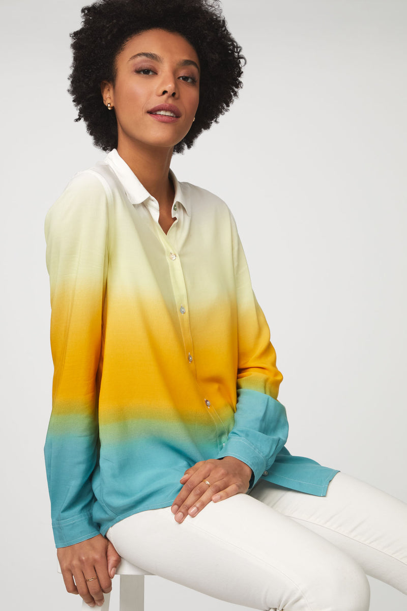 Seated woman wearing a long sleeve, button-down, yellow, blue and white dip dye shirt