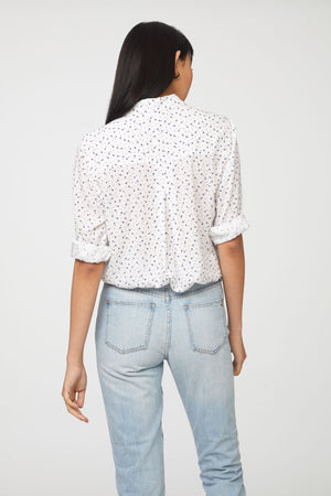back view of woman wearing a long sleeve, button-down, white floral shirt with single chest pocket