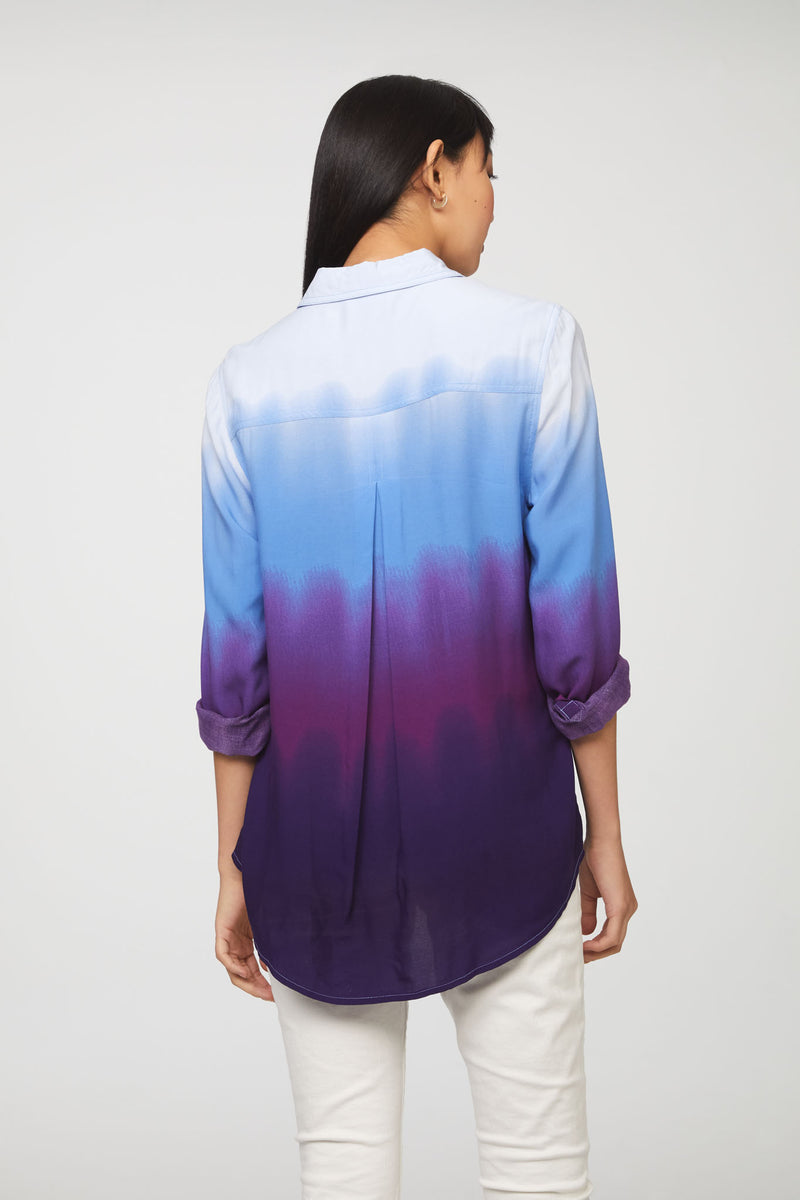 back view of woman wearing a long sleeve, button-down, blue and purple dip dye shirt
