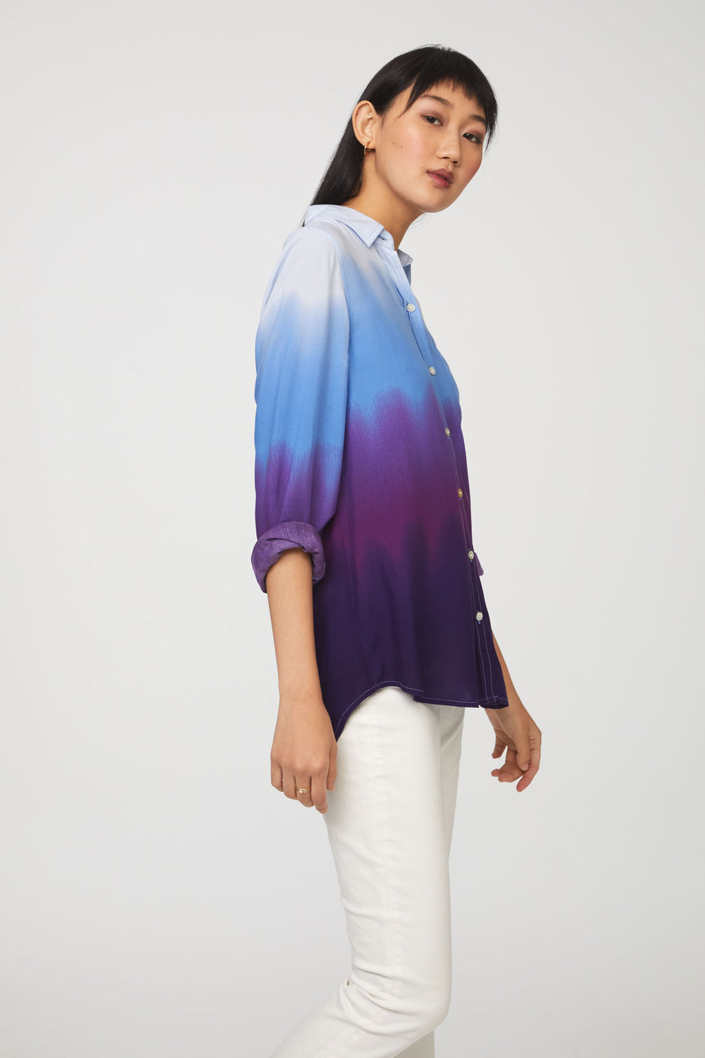 side view of woman wearing a long sleeve, button-down, blue and purple dip dye shirt