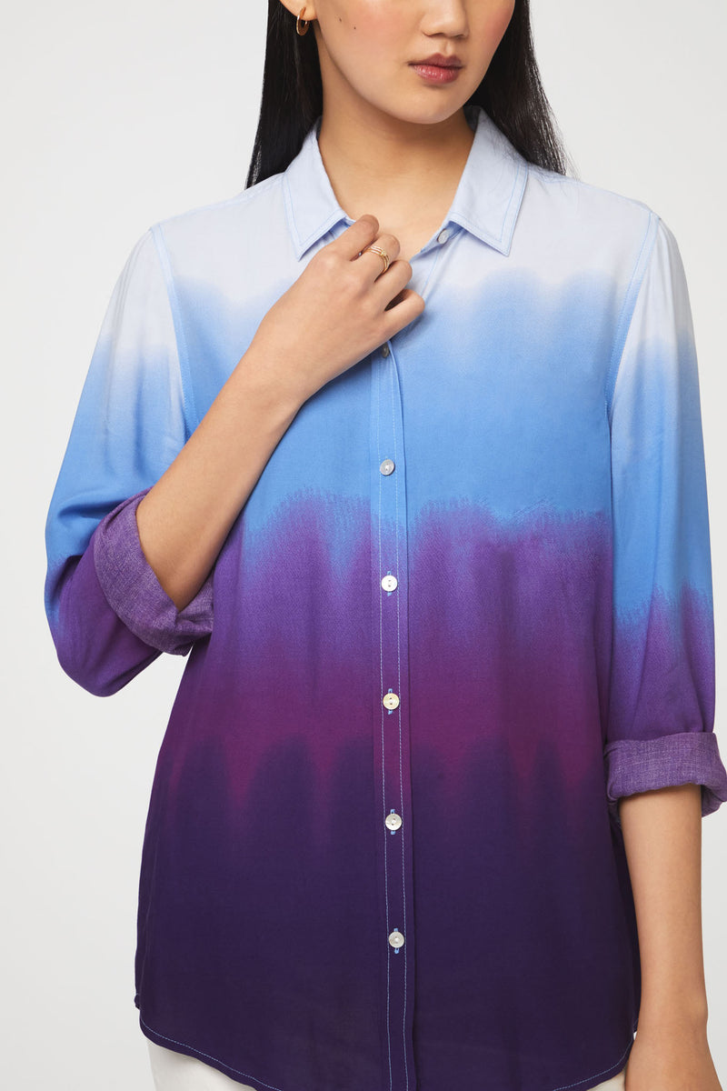 close up of woman wearing a long sleeve, button-down, blue and purple dip dye shirt