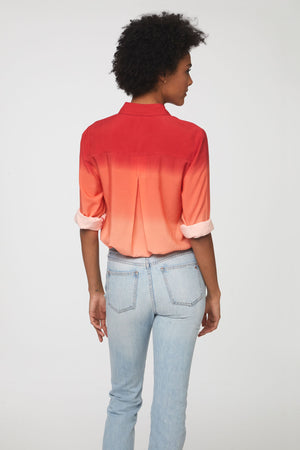 back view of woman wearing a long sleeve, button-down, pink, red, and coral dip dye shirt