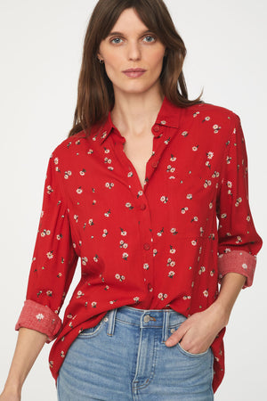 close up of woman wearing a long sleeve, button-down, red floral shirt with single chest pocket