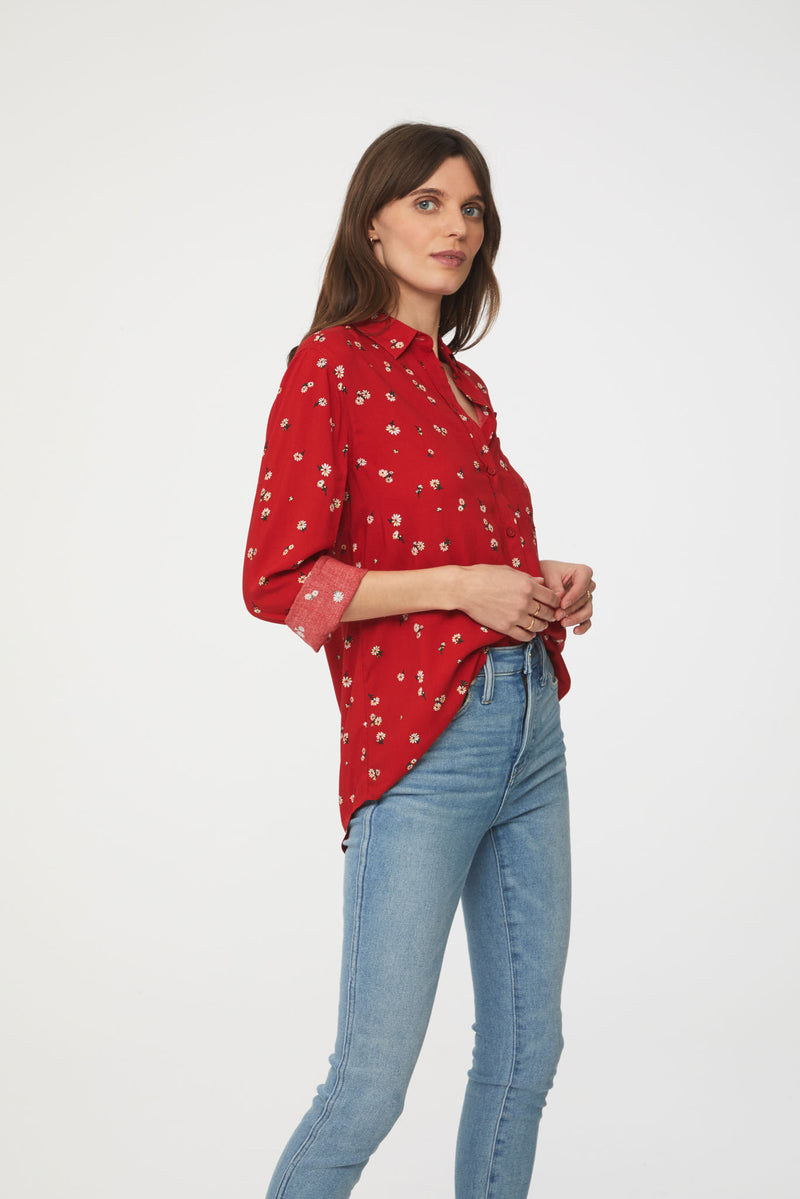 side view of woman wearing a long sleeve, button-down, red floral shirt with single chest pocket