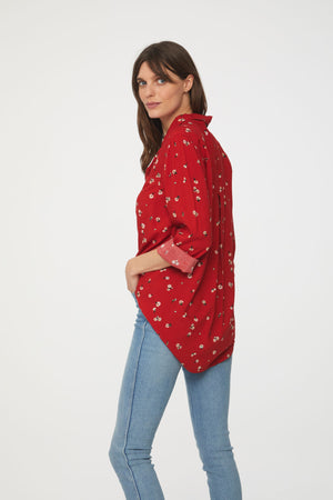 back view of woman wearing a long sleeve, button-down, red floral shirt with single chest pocket