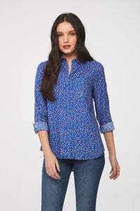 woman wearing a long sleeve, button-down, floral printed blue shirt with single chest pocket