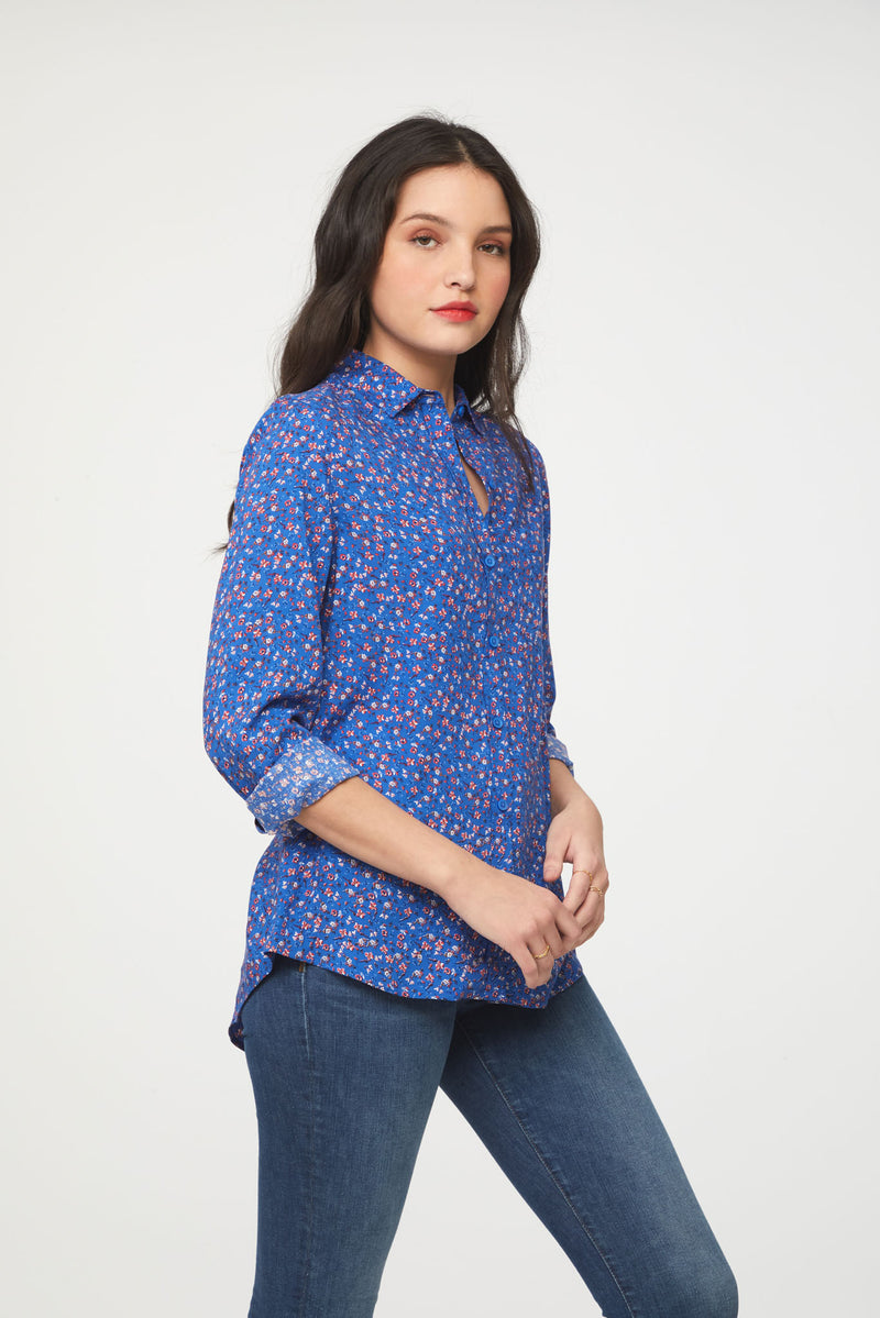 side view of woman wearing a long sleeve, button-down, floral printed blue shirt with single chest pocket