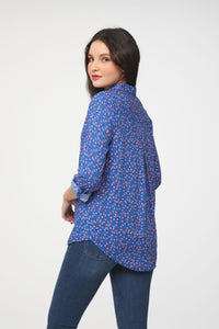 back view of woman wearing a long sleeve, button-down, floral printed blue shirt with single chest pocket