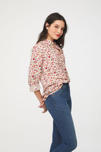side view of woman wearing a long sleeve, button-down, pink floral shirt with single chest pocket
