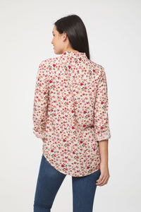 back view of woman wearing a long sleeve, button-down, pink floral shirt with single chest pocket