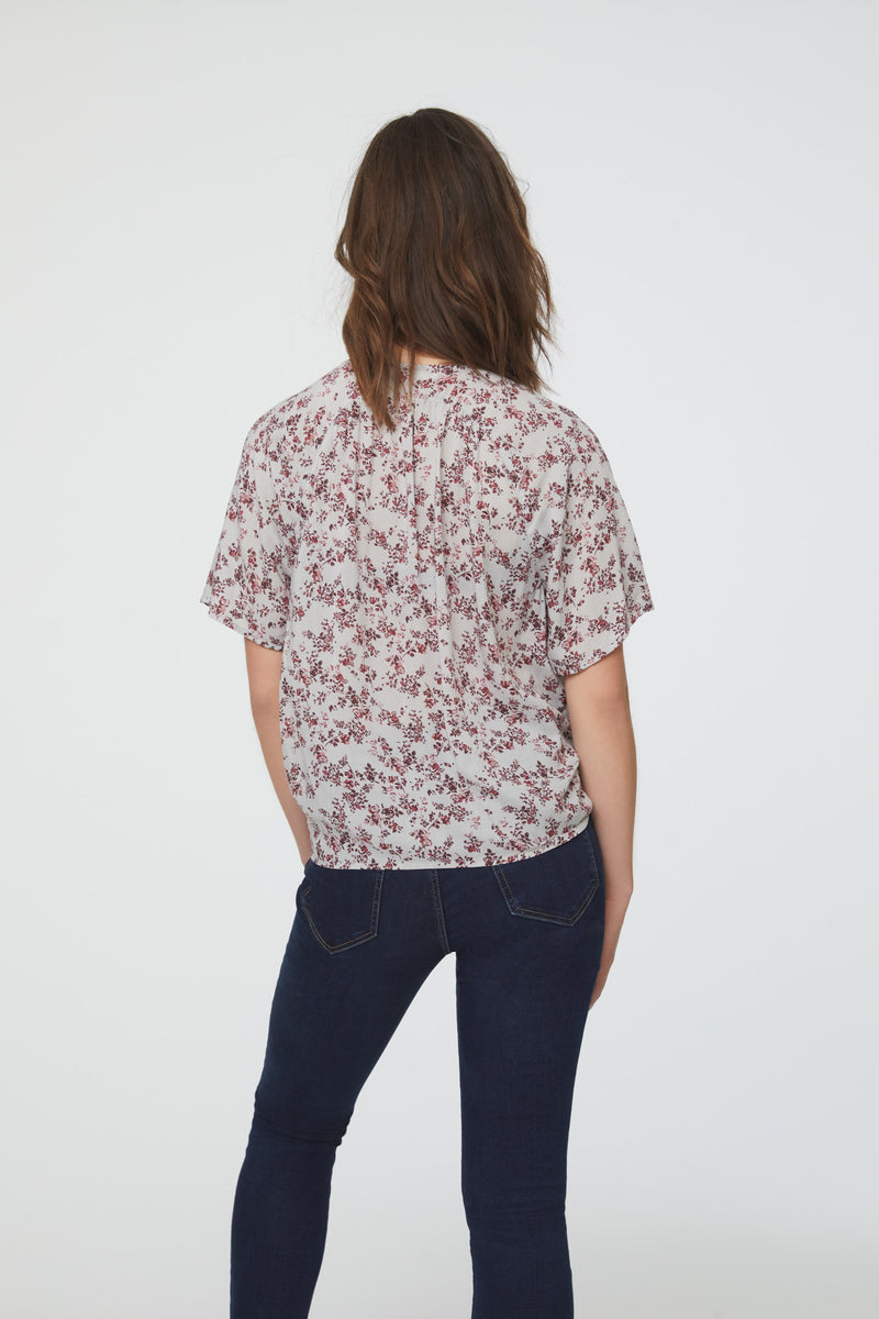 back view of woman wearing a silky, short sleeve, button front v-neck blouse in leopard print with self tie front and drop shoulder