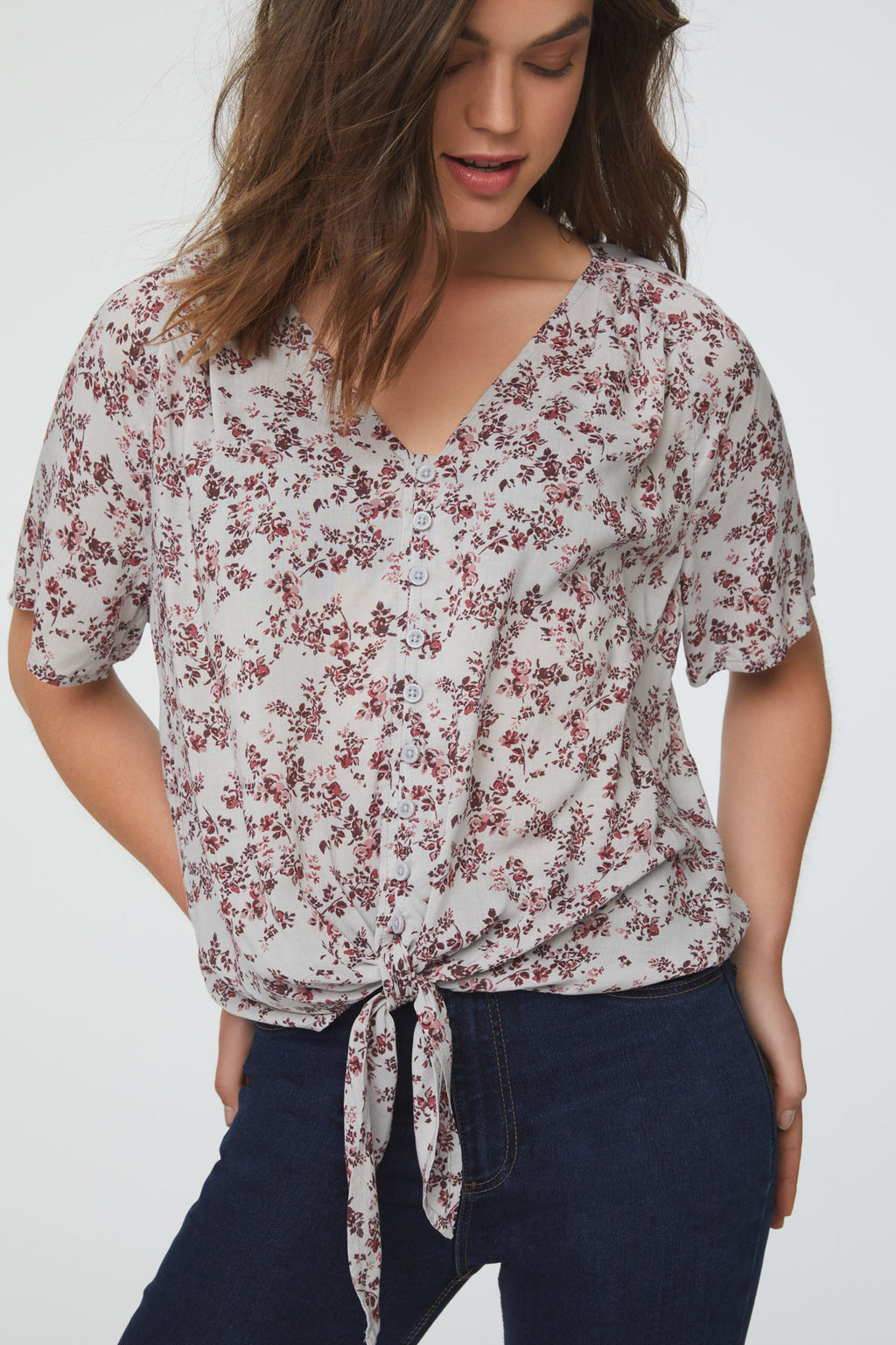 Woman wearing a silky, short sleeve, button front v-neck blouse in vintage floral print with self tie front and drop shoulder