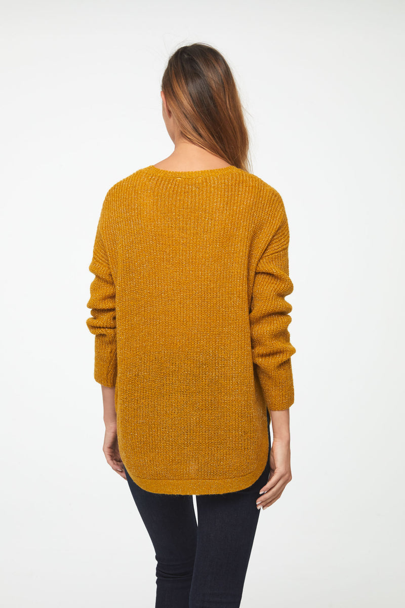 Woman wearing a long sleeve crew neck sweater in yellow mustard color; back