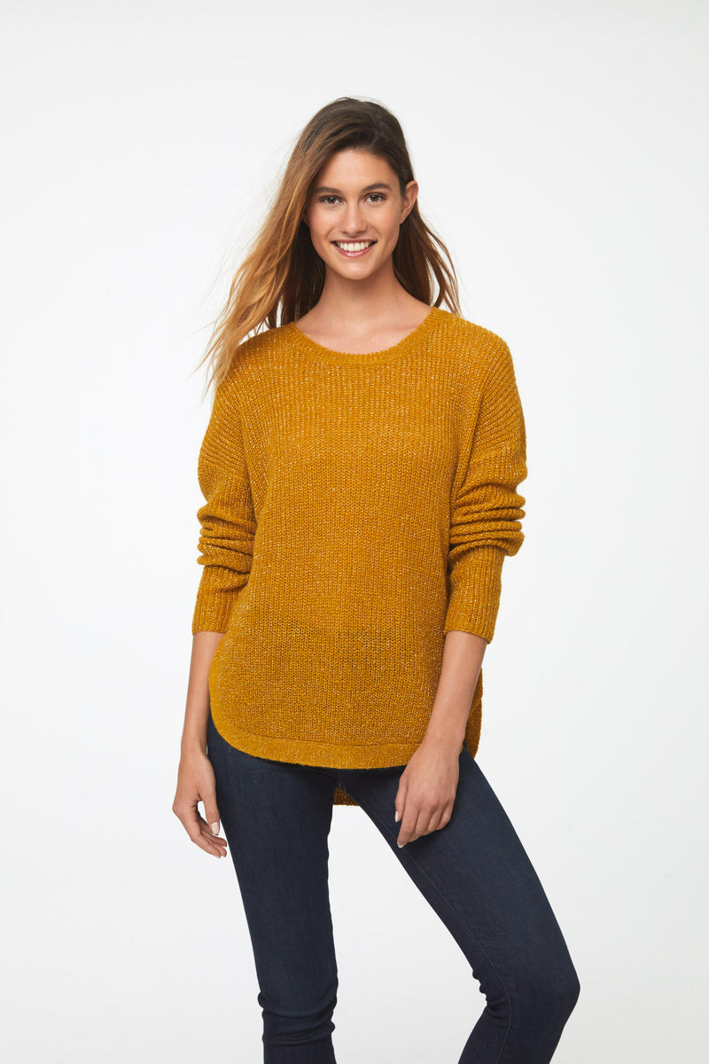 Woman wearing a long sleeve crew neck sweater in yellow mustard color; front
