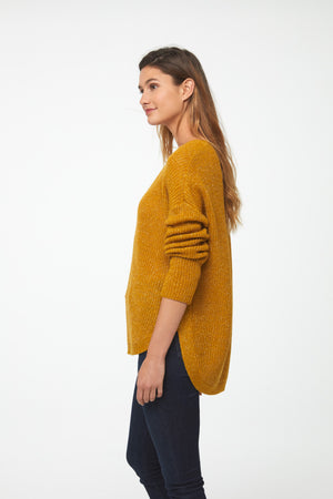 Woman wearing a long sleeve crew neck sweater in yellow mustard color; side