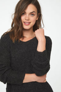 Woman wearing a long sleeve, crew neck sweater in charcoal grey; front