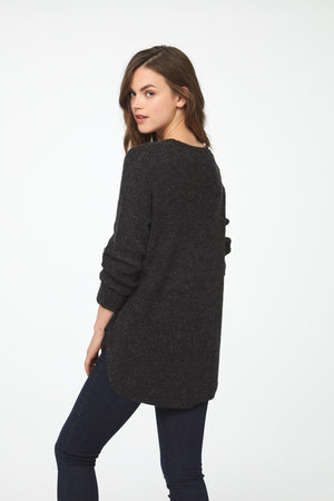 Woman wearing a long sleeve, crew neck sweater in charcoal grey; back