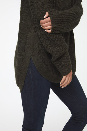 Woman wearing a long sleeve, crew neck sweater in olive green color; side