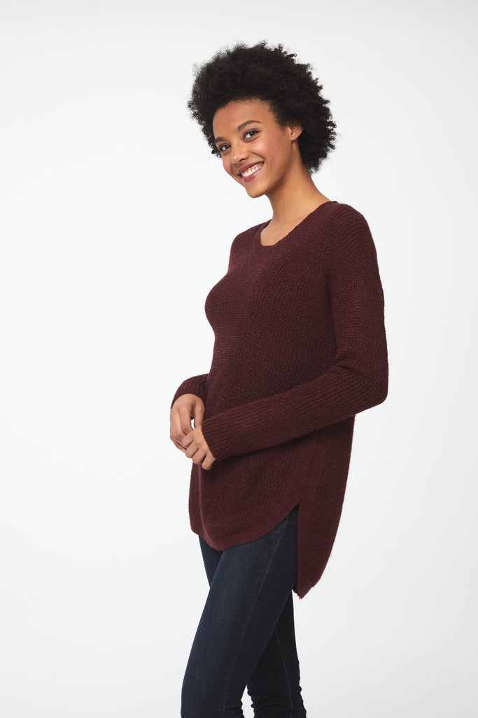 Woman wearing a long sleeve crew neck sweater in burgundy, red; side
