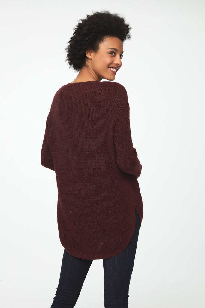 Woman wearing a long sleeve crew neck sweater in burgundy, red; back