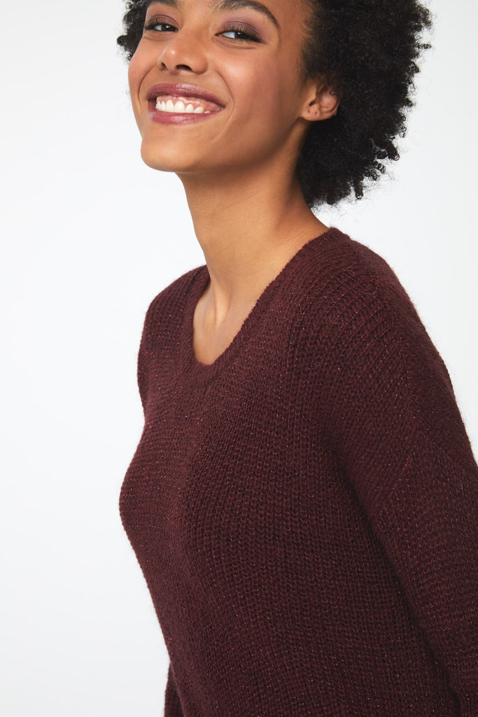 Woman wearing a long sleeve crew neck sweater in burgundy, red; close up