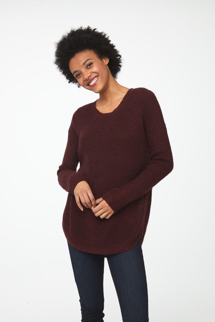 Woman wearing a long sleeve crew neck sweater in burgundy, red; front