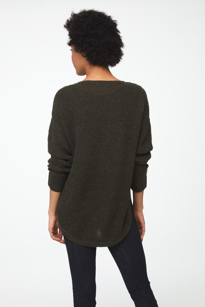 Woman wearing a long sleeve, crew neck sweater in olive green color; back