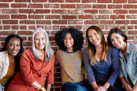 Women in front of a red brick wall