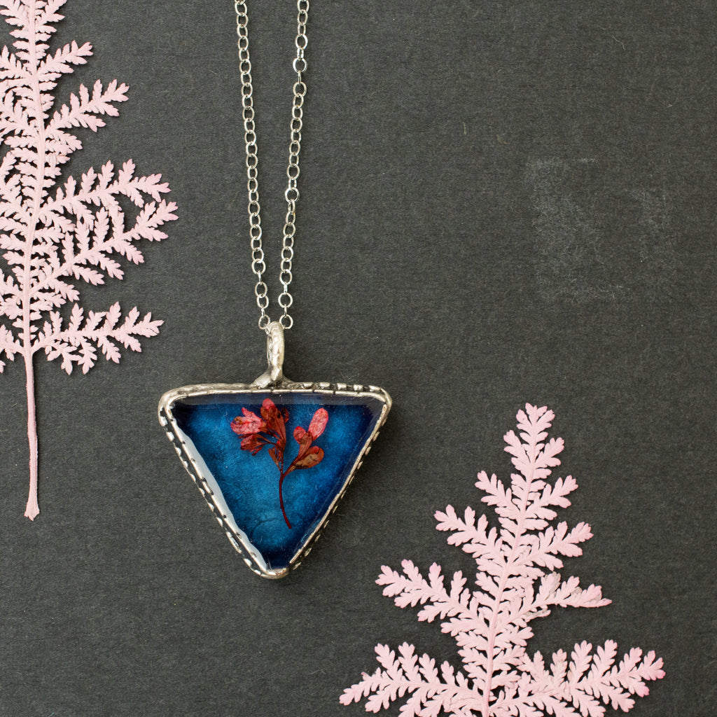 Blue triangle pendant with red wildflowers