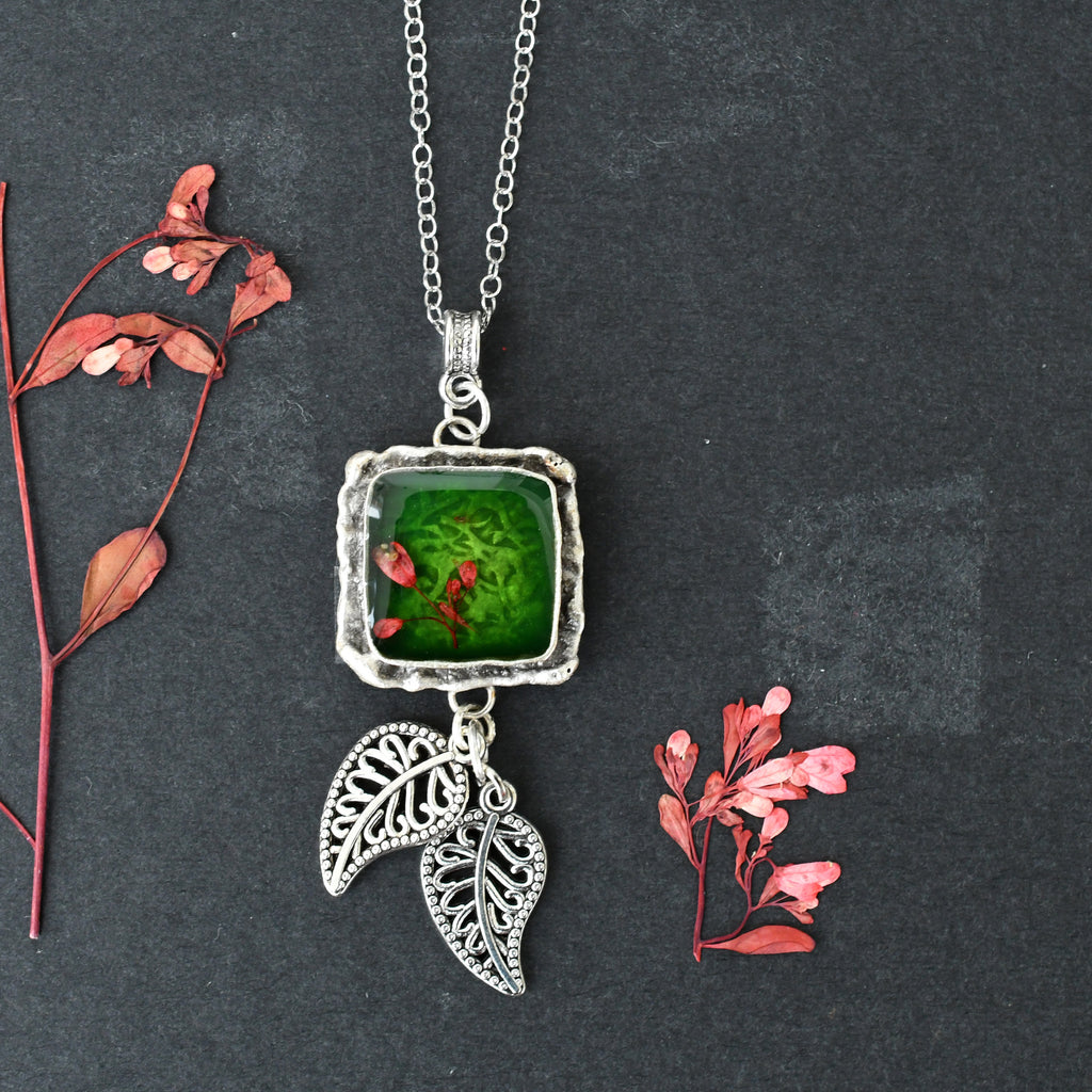 Green pendant with leaf charm