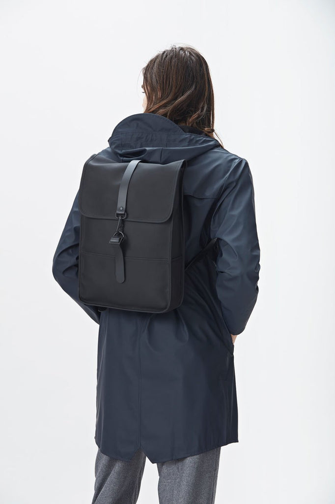The biggest selection of bags satches murses and backpacks in vancouver Rains Waterproof Backpack Mini in Black on male model