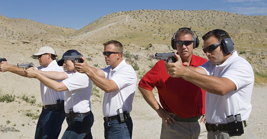 instructor assisting men firing range