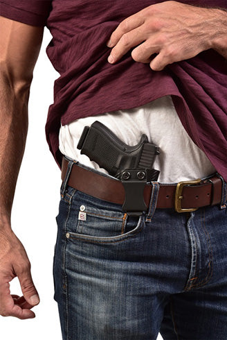 man lifting shirt waistband holster