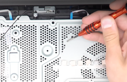 Removing the 10 screws that hold the metal heatsink in place