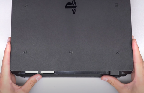 Sliding the bottom cover on from the front of the console to the back