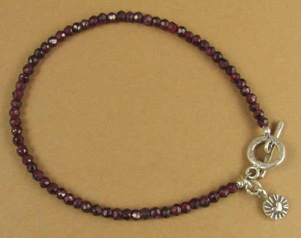 Red garnet bracelet with heart charm. Faceted. Fine and sterling silver.