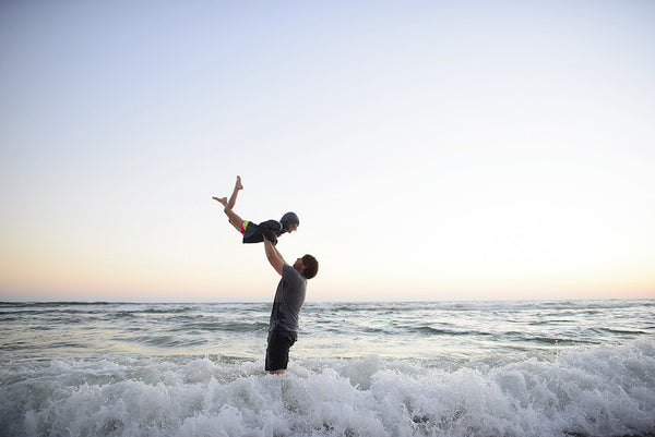 father throwing daughter in the air in the ocean