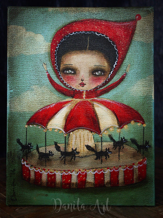 A surreal illustration of wolves as merry go round figures dance around Little Red Riding Hood on this original painting by Danita.