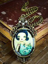 The knitter of the sea, a surreal painting by Danita adorns this beautiful handmade big necklace.