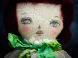 A beautiful face, a hand made lace dress and a ribbon make this fabric art doll by Danita an amazing work of art