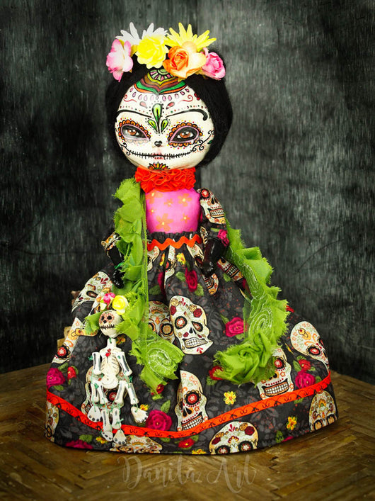 Frida Kahlo is dressed as a colorful painted skull on this original hand crafted art doll by Danita Art