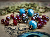 Beautiful faceted turquoise and deep red beads take part to create an maxing handmade wearable art piece in this handcrafted necklace with a surreal image of a girl in mask, by Danita Art