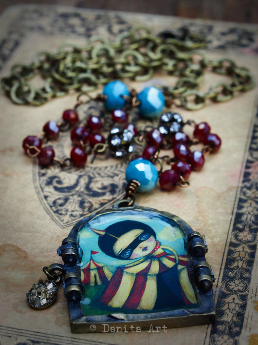 The discovery is a handcrafted necklace with gold, blue and red faceted beads, a circus tent surreal girl and a deep meaning, inspired by self discovery and exploration, from the times where we learned we came into womanhood.