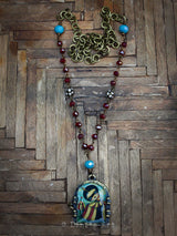 This handcrafted necklace by Danita Art will draw looks whenever you wear it. It's inviting image of a girl in a mask and circus themed dress, along with red and turquoise glass and natural stone faceted beads is much more than it seems, just like you.